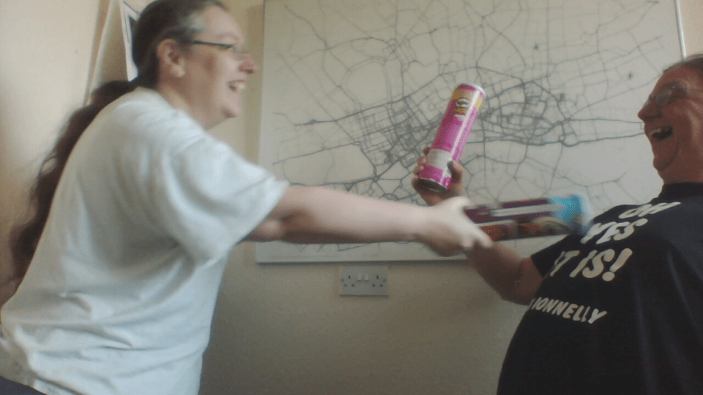 Jen and Robin are pretending to sword fight with Pringles tubes.
