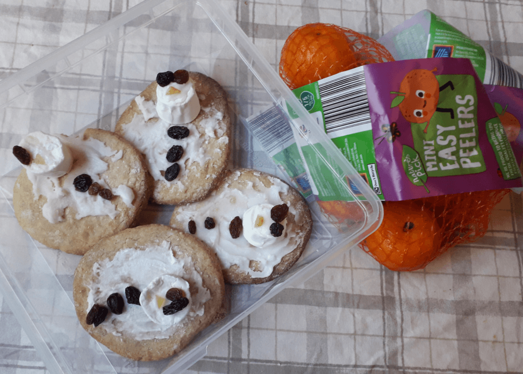 Several clearly homemade biscuits decorated as melting snowmen, and a bag of clementines.